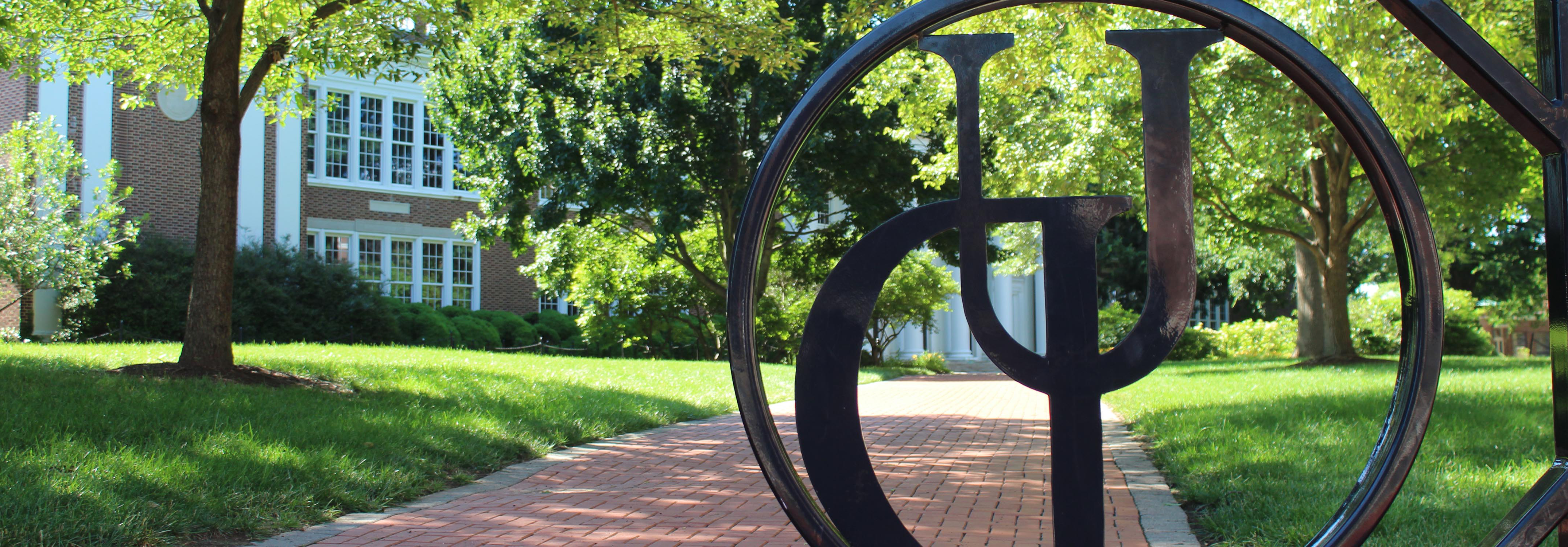 Up close view of a black fence with the monogram logo of UD built into it. Blurry trees and brick path are in the background.