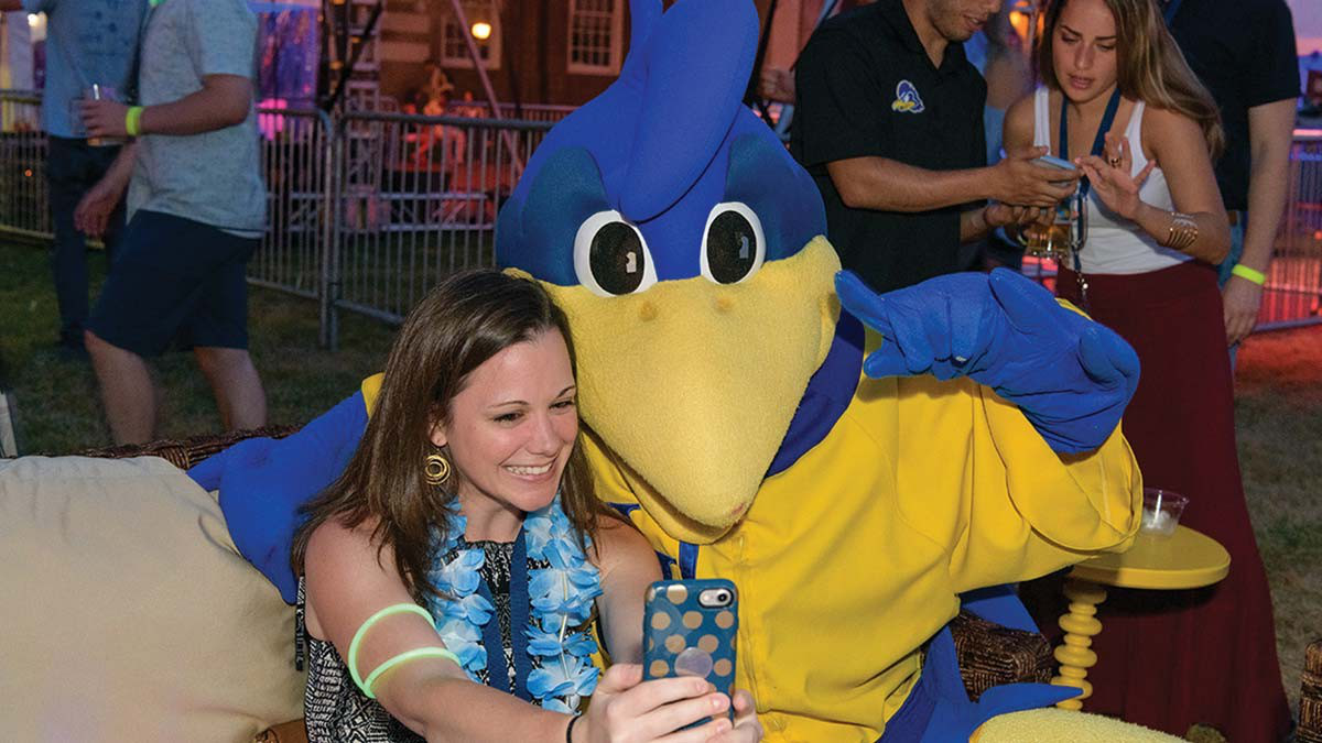 A woman takes a selfie with YouDee at an University of Delaware event.